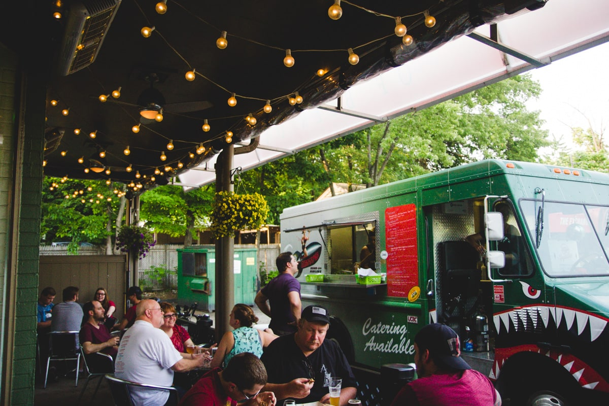 people sitting outside 101 bottles patio with parked food truck
